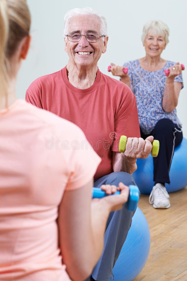 Seniors At Fitness Class With Instructor. Seniors At Fitness Class With Female Instructor royalty free stock image