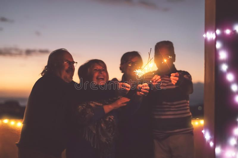 Seniors friends having fun celebrating holidays together outdoor - Happy older people enjoying party laughing on terrace at sunset. Time - Elderly lifestyle royalty free stock images