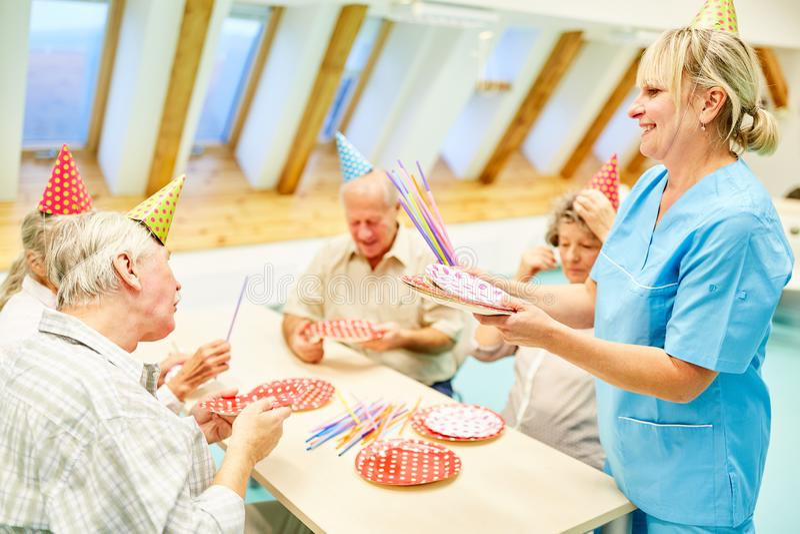 Seniors and a geriatric nurse celebrate together stock photo