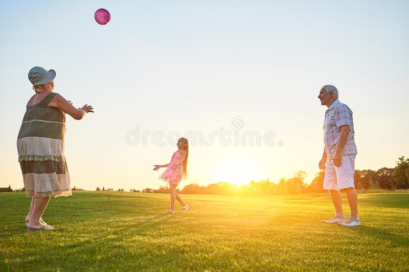 Seniors with grandchild playing ball. People having fun outdoors. Best lawn games for families royalty free stock image
