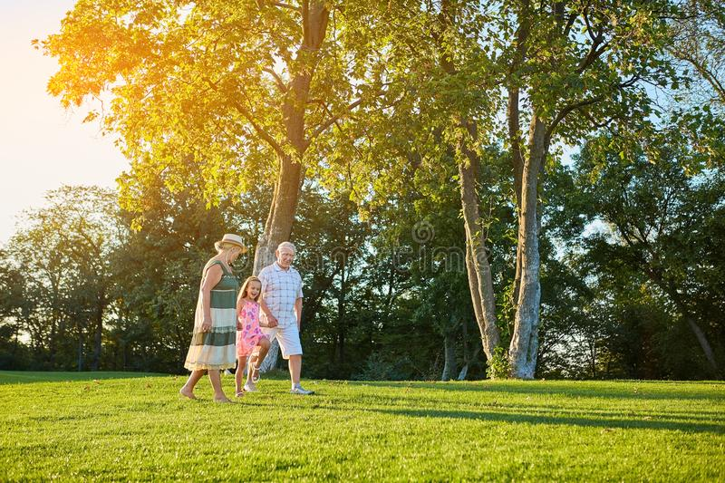 Seniors with grandchild walking outdoors. stock photos