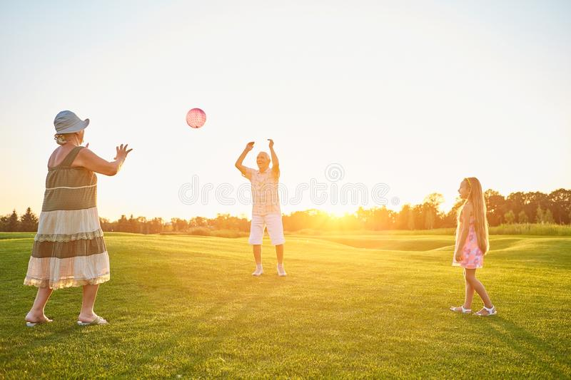 Seniors with granddaughter playing ball. royalty free stock photography