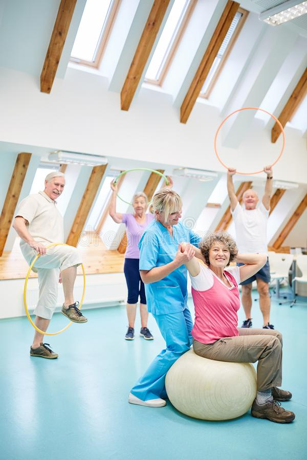 Seniors in the gym class have fun. Seniors in the gymnastics class have fun with a physiotherapy trainer stock photography