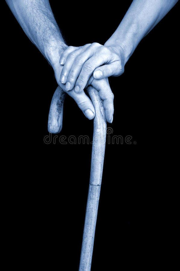 Seniors hands holding walking stick. People body parts royalty free stock image