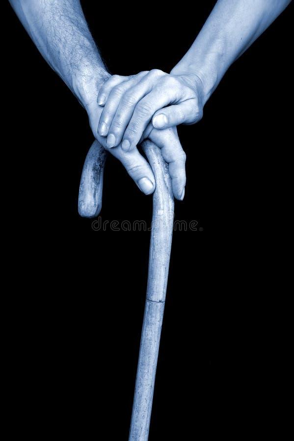 Seniors hands holding walking stick royalty free stock image