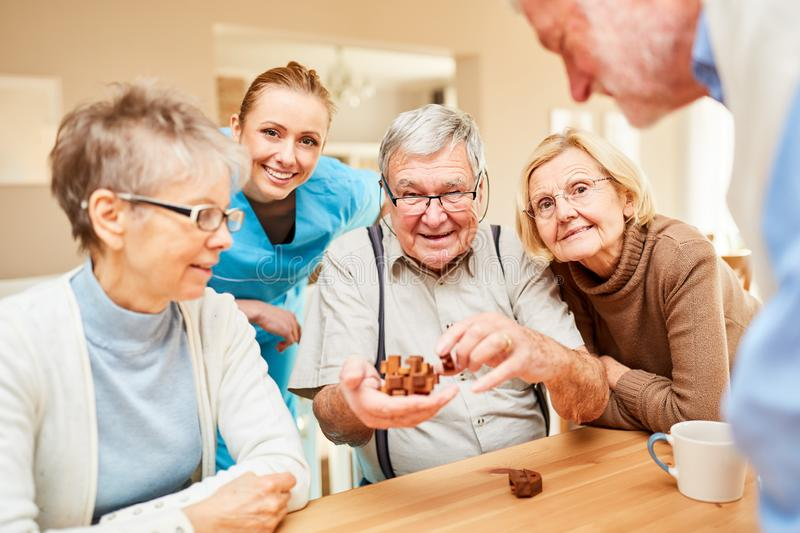 Seniors have fun with a wooden puzzle royalty free stock photo