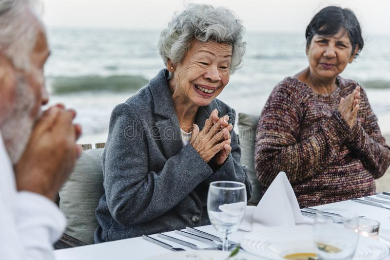 Seniors having a dinner party at the beach stock image