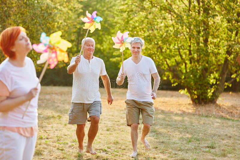 Seniors having fun in the park. And holding pinwheels royalty free stock image