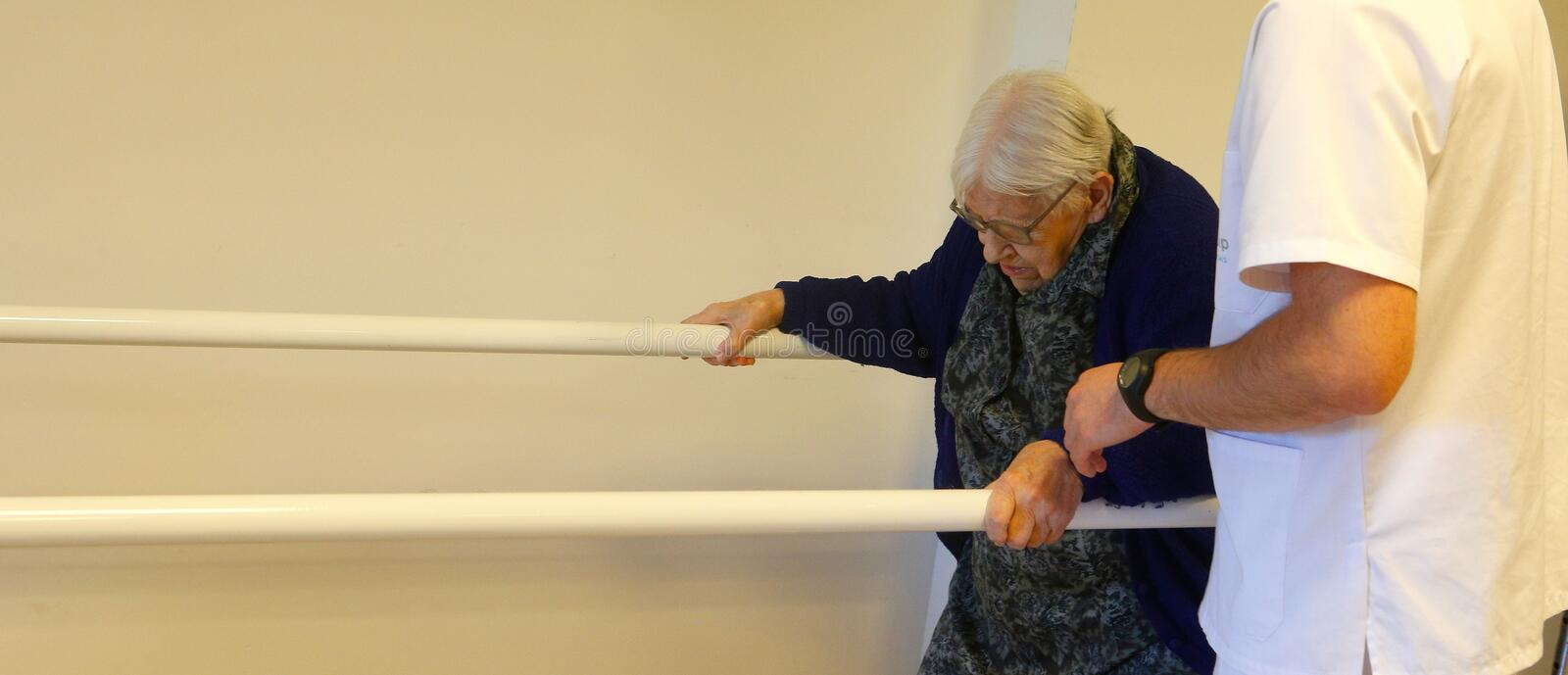 Senior woman during therapeutical activities on a nursing home in Mallorca wide. Seniors with the help of a male nurse practice some coordination exercise on the stock photo