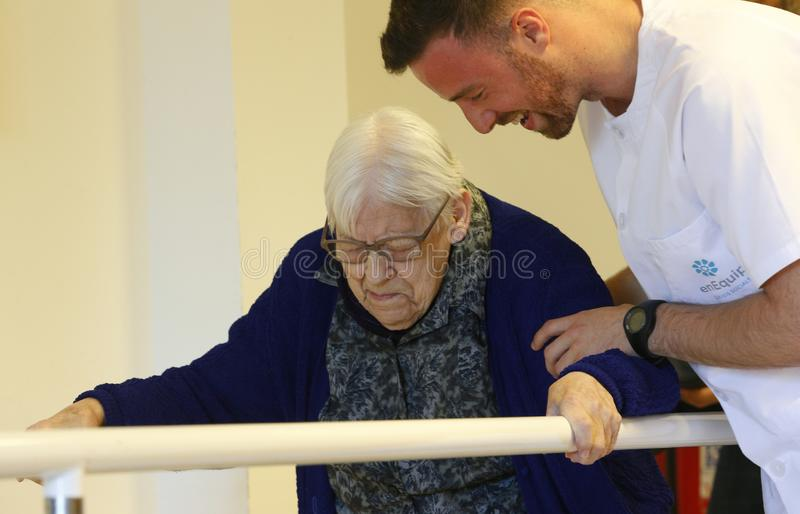 Senior woman during therapeutical activities on a nursing home in Mallorca. Seniors with the help of a male nurse practice some coordination exercise on the gym royalty free stock image