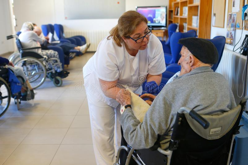 Seniors and nurse during their daylife on a nursing home in Mallorca. Seniors are helped and cared by nurses inside their nursing home in the Spanish island of royalty free stock photography