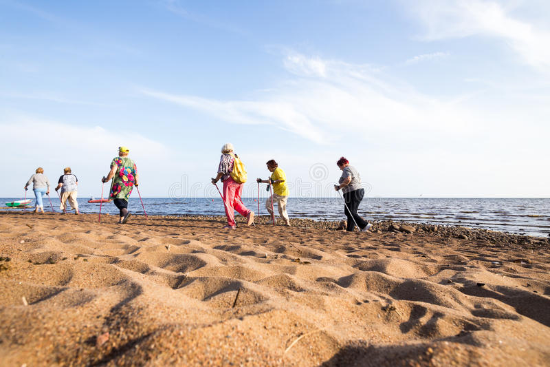 Seniors hiking on the seashore. Finnish Gulf, Saint Petersburg, Russia, 25 july 2016 stock photos