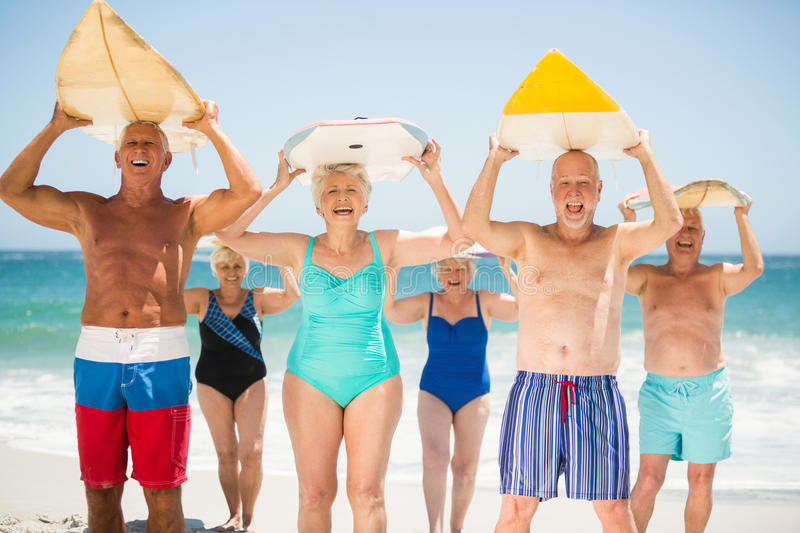 Seniors holding surfboards at the beach. On a sunny day stock image