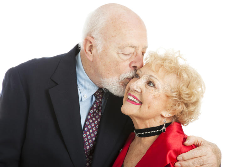 Seniors - Holiday Kiss. Adorable senior woman getting a romantic holiday kiss from her husband. Isolated on white royalty free stock photo