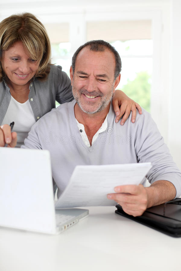 Seniors at home doing paperwork royalty free stock images