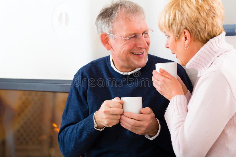 Seniors at home in front of fireplace. With tea cup royalty free stock photo