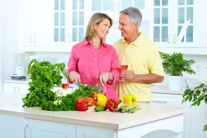 Seniors at kitchen. Happy seniors couple cooking at kitchen royalty free stock photo