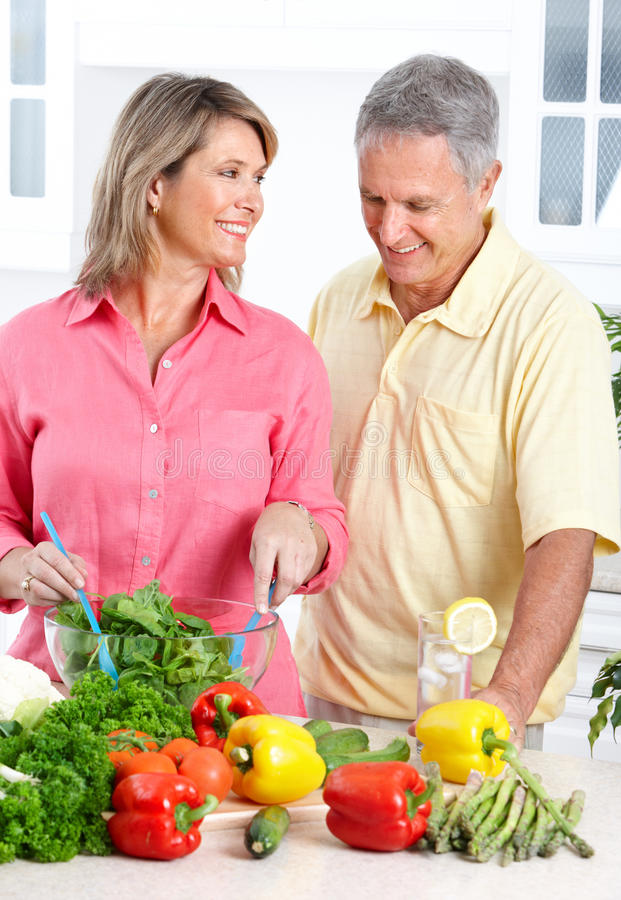 Seniors at kitchen. Happy seniors couple cooking at kitchen