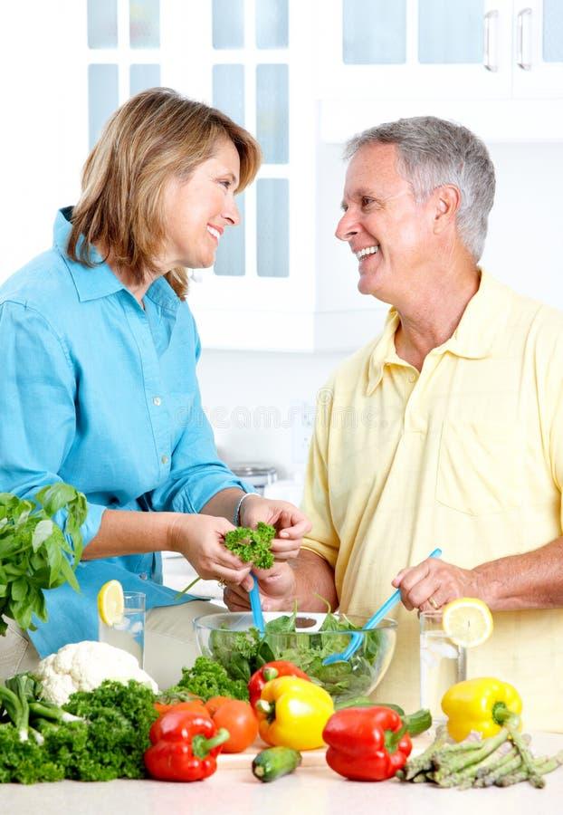 Seniors at kitchen. Happy seniors couple cooking at kitchen stock photo