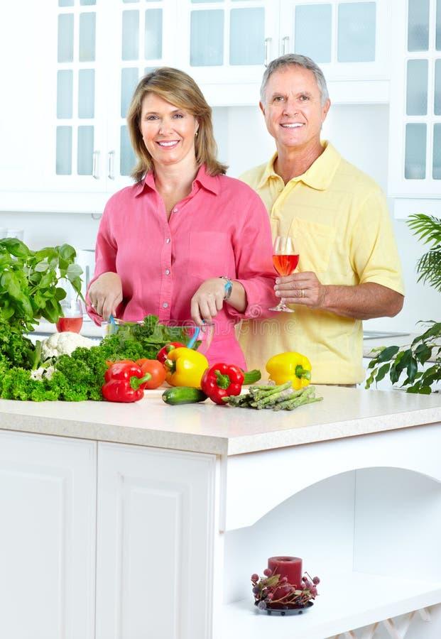 Seniors at kitchen. Happy seniors couple cooking at kitchen stock photography