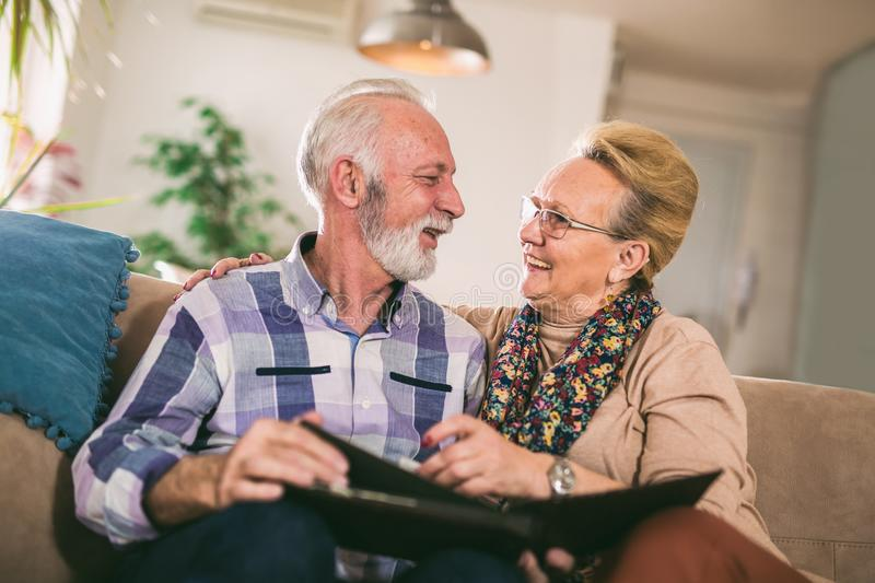 Seniors looking at their photo album. At home royalty free stock image