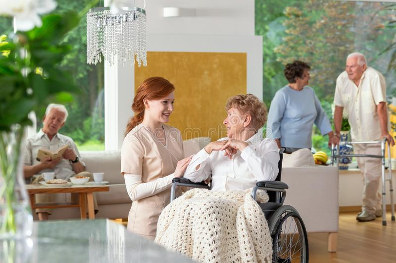 Seniors in a luxury living room of a private retirement home. Te. Nder caregiver by an elderly lady in a wheelchair in the foreground stock photos