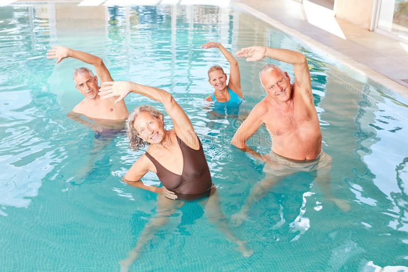 Seniors make healthy stretching in a course. For aquagym stock photos