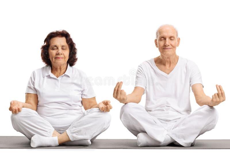 Seniors meditating on an exercise mat stock photo