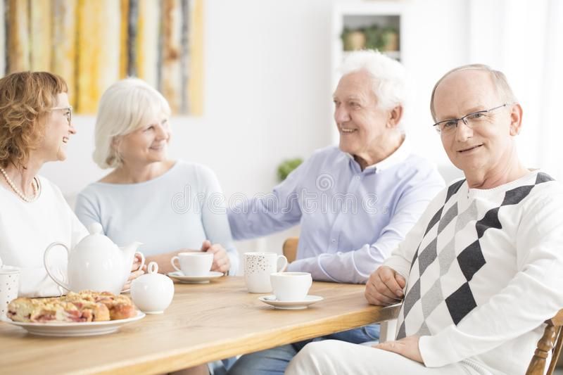 Seniors in nursing home. A group of seniors talking and eating at a table in a nursing home stock photography