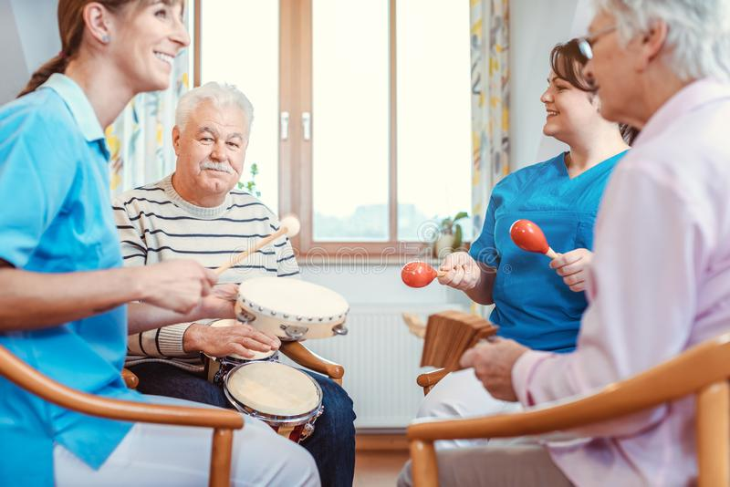 Seniors in nursing home making music with rhythm instruments. As musical therapy stock photography