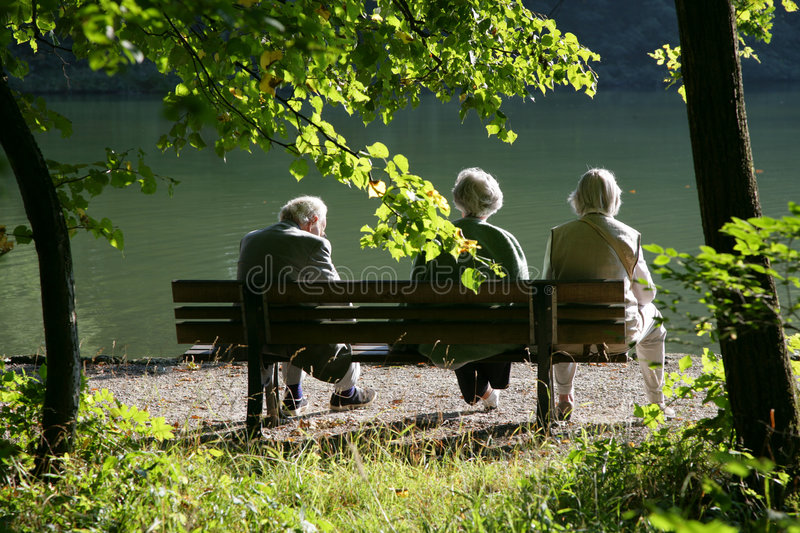 Seniors on a park bench stock image