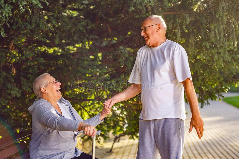 Seniors in park- Old man caring wife in the park. Seniors in park- Smiling old men caring wife in the park stock photo