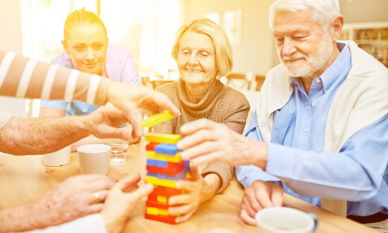 Seniors play with building blocks in the nursing home. Friendly seniors play together with colorful building blocks in the nursing home stock photos