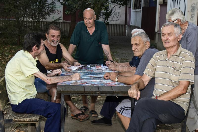 Seniors play cards. ZRENJANIN, SERBIA, SEPTEMBER 05,2019. A group of senior citizens mostly retirees having fun playing cards outdoors in the park stock image