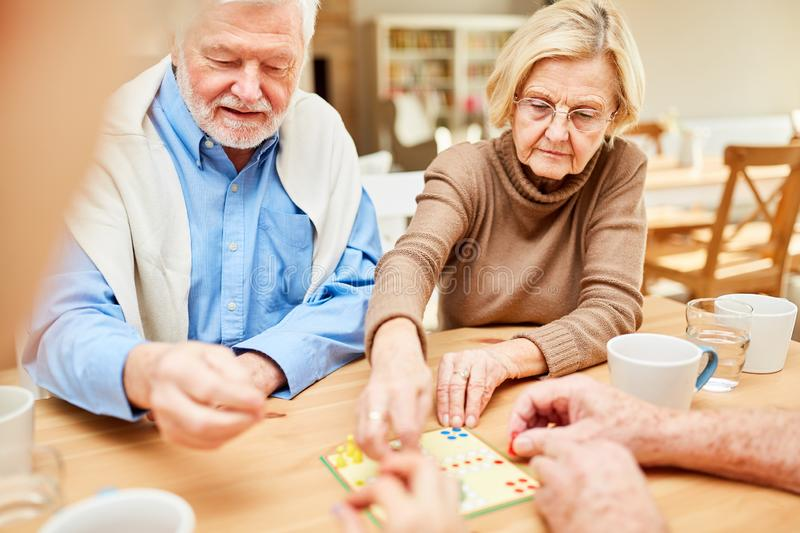 Seniors play board game in retirement home or retirement home. Seniors play together a board game in a nursing home or retirement home royalty free stock photo