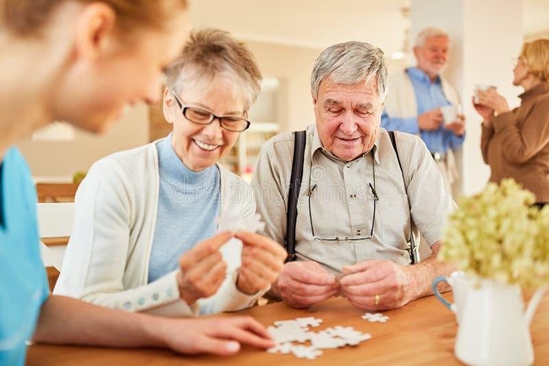 Seniors playing Alzheimer`s puzzle stock photo