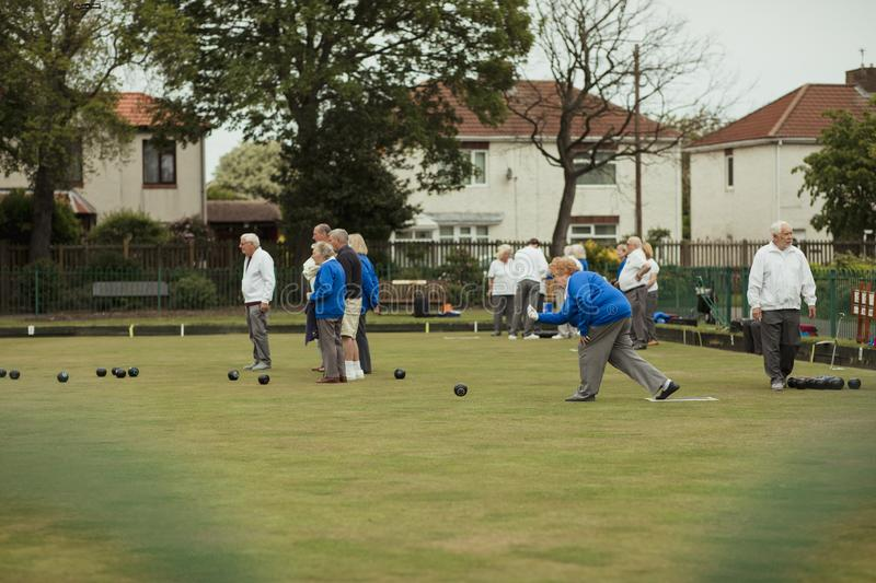 Seniors Playing Lawn Bowling. A side view shot of a senior women taking her shot in a game of lawn bowling, surrounded by other seniors in the community stock images