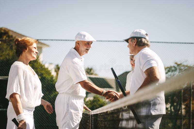 Seniors playing mixed doubles tennis game. Senior men shaking hands standing on tennis court after the game. Seniors greeting each other after a game of mixed royalty free stock images