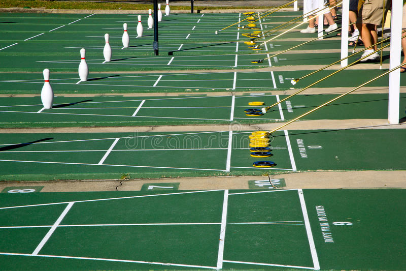 Seniors Playing Shulleboard in Florida. Seniors playing shuffleboard on a green court at a resort in Florida, The game has just started. The players are in royalty free stock photography