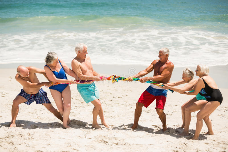 Seniors playing tug of war at the beach. On a sunny day stock photo