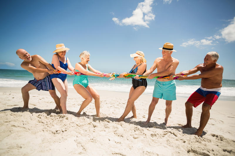 Seniors playing tug of war at the beach royalty free stock photos