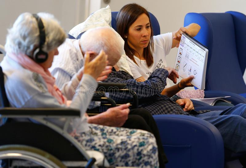 Seniors and nurse during therapeutical mind activities on a nursing home in Mallorca. Seniors practice with the help of a nurse some mind activities and games on royalty free stock photos