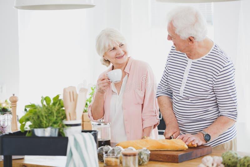Seniors preparing breakfast together royalty free stock photography