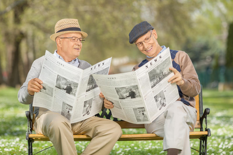 Seniors reading newspaper in a park. Senior gentleman showing something in the newspaper to a friend seated on a wooden bench in a park stock images