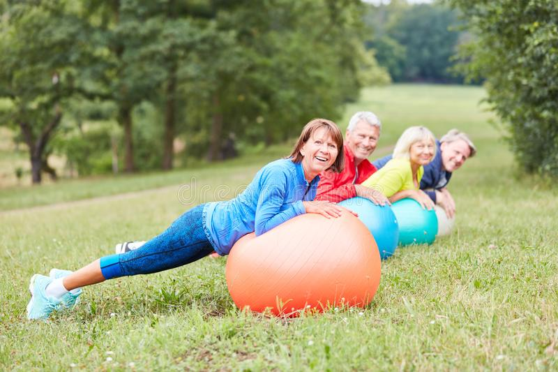 Seniors in the rehabilitation course do back training. Senior in rehabilitation class doing healthy back training with exercise ball royalty free stock photography