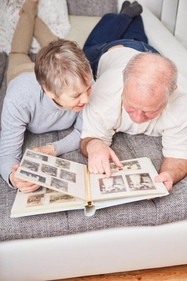 Seniors in retirement hold photo album. And look at it royalty free stock photos