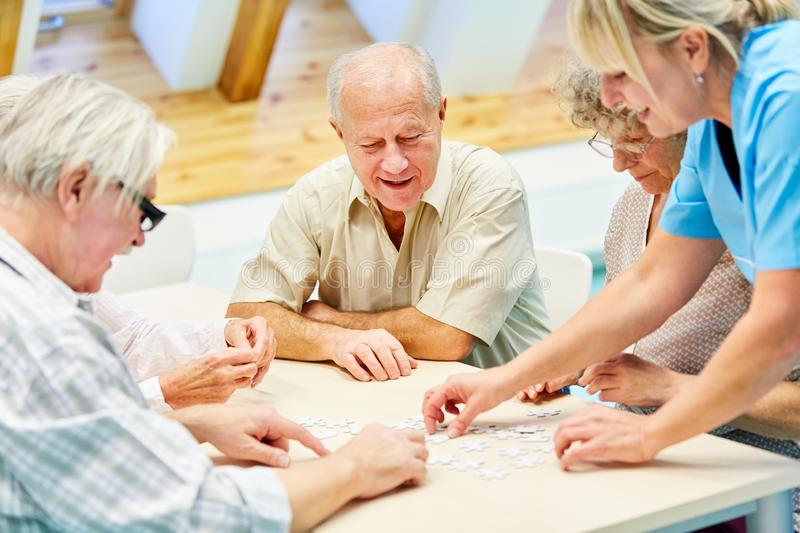 Seniors in retirement home playing with puzzle. Group of seniors in retirement home while playing with puzzle cared for by a nursing assistant royalty free stock photo
