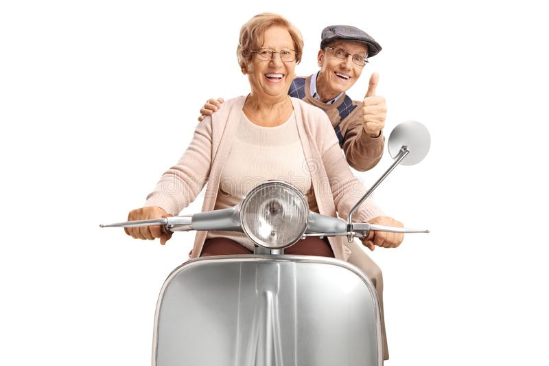 Seniors riding a retro scooter making a thumb up gesture. Isolated on white background stock images