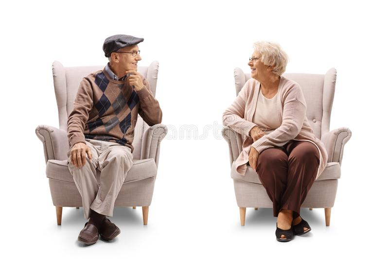 Seniors sitting in armchairs and having a conversation royalty free stock photos