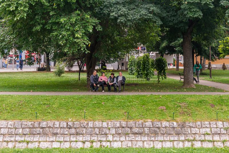 Seniors are sitting on a bench in a park in Loznica, Serbia. royalty free stock photos
